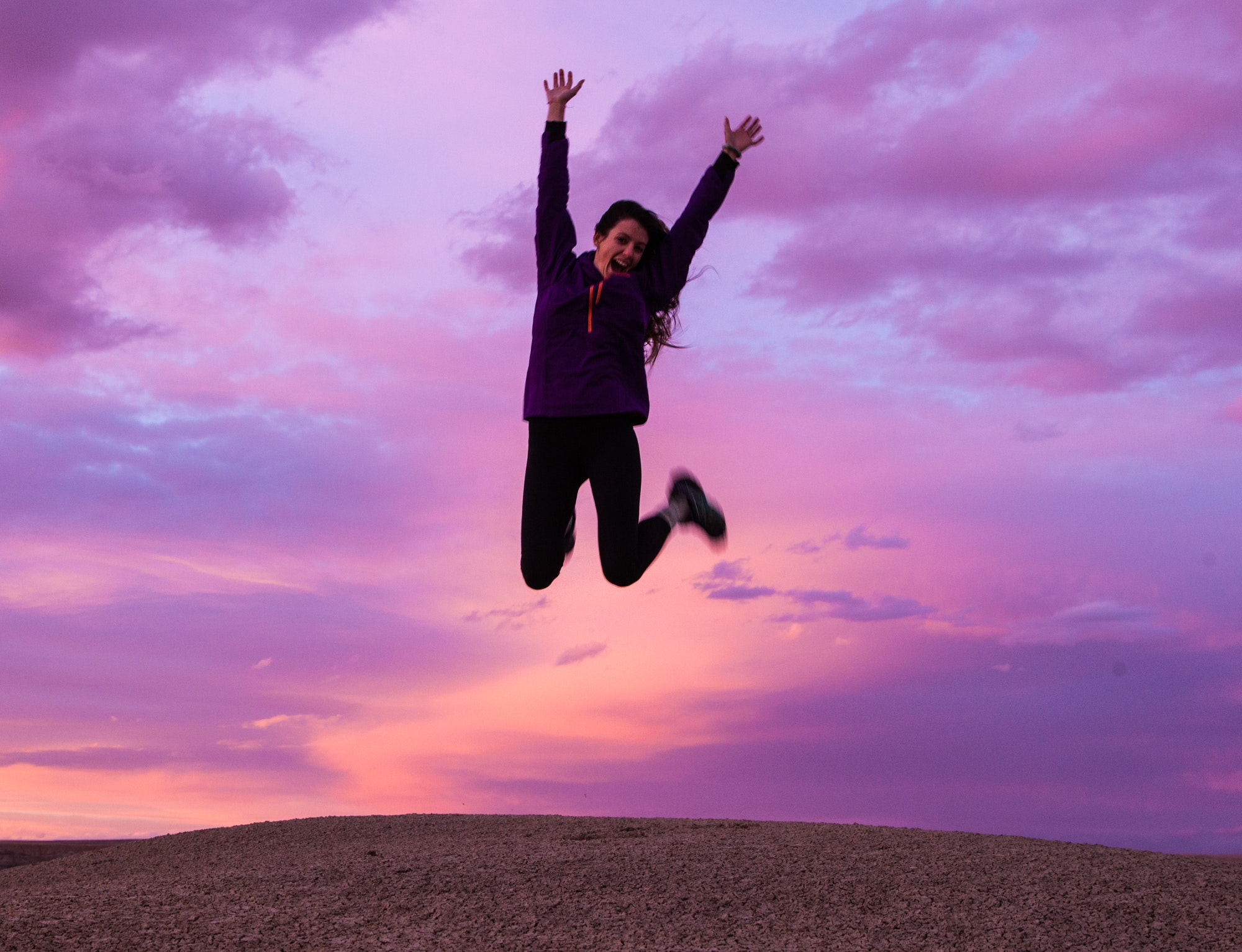 woman jumping purple sky